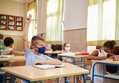 masked boy sitting in classroom raising his hand